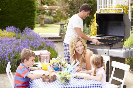 niños cocinando: Familia que disfruta de la barbacoa al aire libre en el jardín