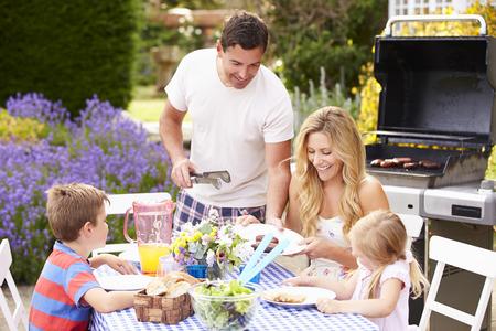 parrillada: Familia que disfruta de la barbacoa al aire libre en el jardín