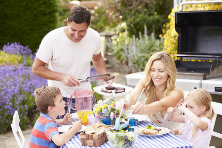 Familia que disfruta de la barbacoa al aire libre en el jardín Foto de archivo - 31009543