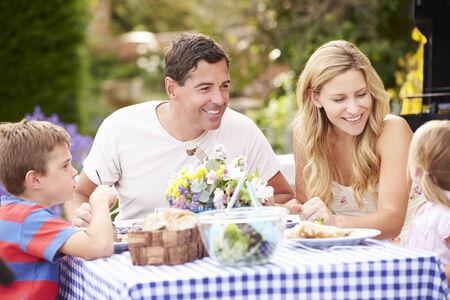 family garden: Family Enjoying Outdoor Meal In Garden