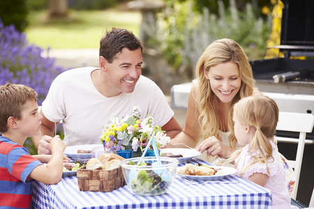 Family Enjoying Outdoor Meal In Garden