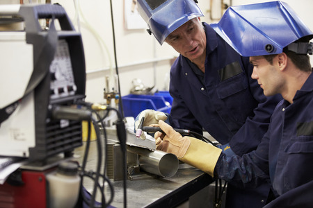 soldador: Ingeniero Aprendiz de enseñanza utilizar máquina de soldadura TIG Foto de archivo