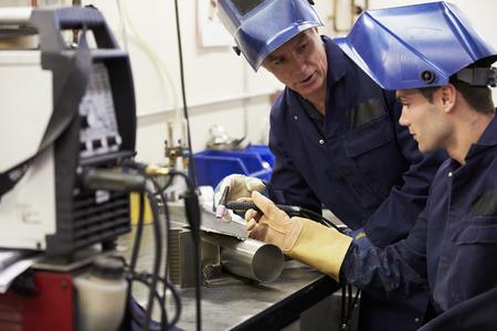 ingeniero: Ingeniero Aprendiz de ense�anza utilizar m�quina de soldadura TIG Foto de archivo
