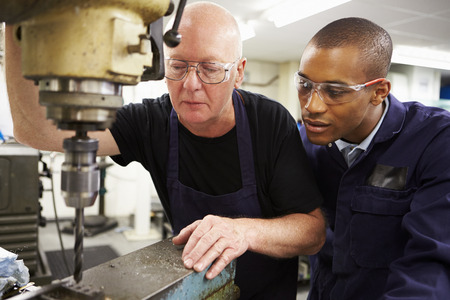apprentice: Engineer Teaching Apprentice To Use Milling Machine Stock Photo