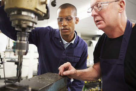 Engineer Teaching Apprentice To Use Milling Machine Imagens
