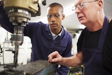 Engineer Teaching Apprentice To Use Milling Machine photo