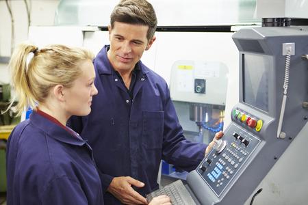 자동 밀링 머신을 사용하는 엔지니어 및 견습생