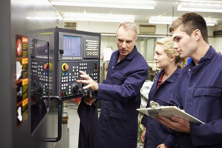 ingeniero: Ingeniero conocimientos a aprendices utilizar Torno computarizada Foto de archivo