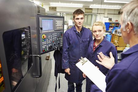 コンピューター化された旋盤を使用するには、エンジニア教育実習生