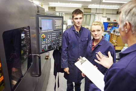 apprentice: Engineer Teaching Apprentices To Use Computerized Lathe