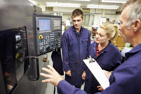 working: Engineer Teaching Apprentices To Use Computerized Lathe