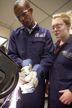 Engineer Teaching Apprentice To Use Grinding Machine photo