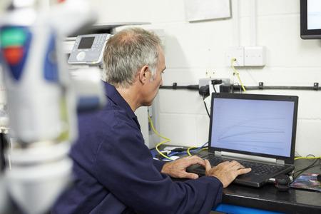 工場でコンピューター化された CMM 腕を使用する技術者