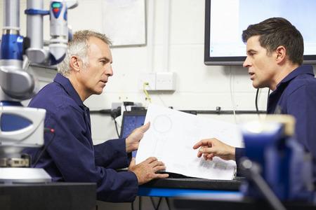 Twee ingenieurs bespreken van plannen Met CMM Arm In Voorgrond
