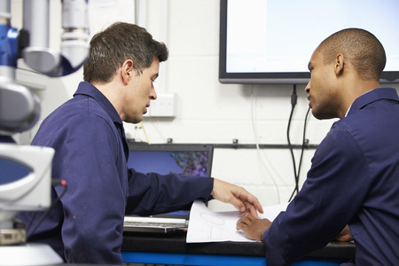 Two Engineers Discussing Plans With CMM Arm In Foreground Stockfoto