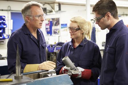Engineer Working With Apprentices On Factory Floor