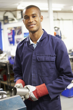 factory worker: Apprentice Engineer Working On Factory Floor Stock Photo