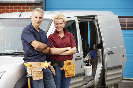 Workers In Family Business Standing Next To Van photo