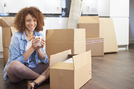 relocate: Woman Moving Into New Home And Unpacking Boxes