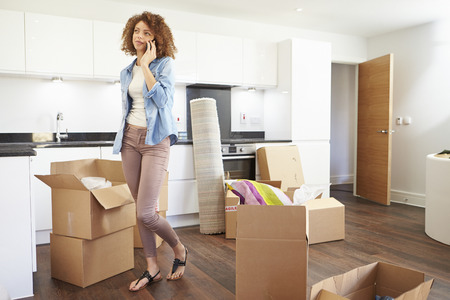 house call: Woman Moving Into New Home Talking On Mobile Phone
