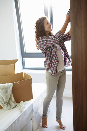 relocate: Woman Moving Into New Home And Unpacking Boxes In Bedroom