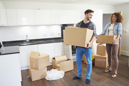 man carrying box: Couple Moving Into New Home And Unpacking Boxes