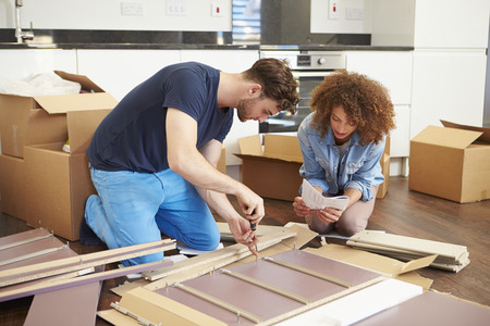 self assembly: Couple Putting Together Self Assembly Furniture In New Home Stock Photo