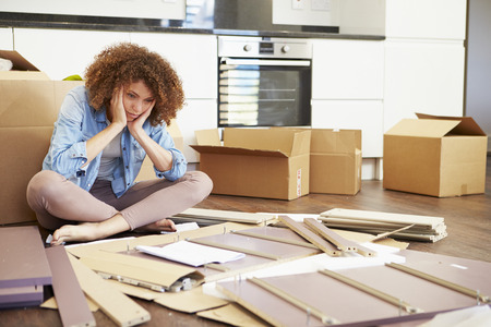 Frustrated Woman Putting Together Self Assembly Furniture photo