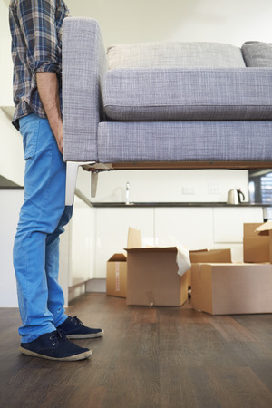 moving up: Close Up Of Man Carrying Sofa As He Moves Into New Home