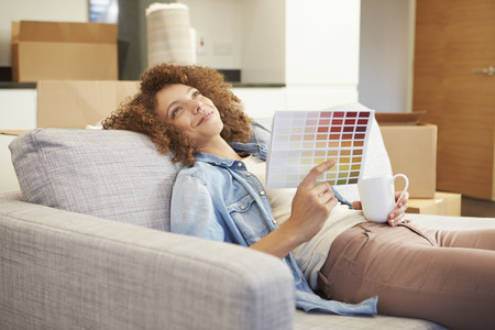 property: Woman Sitting On Sofa Looking At Paint Charts