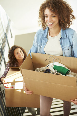 moving box: Two Women Moving Into New Home Carrying Box Upstairs Stock Photo