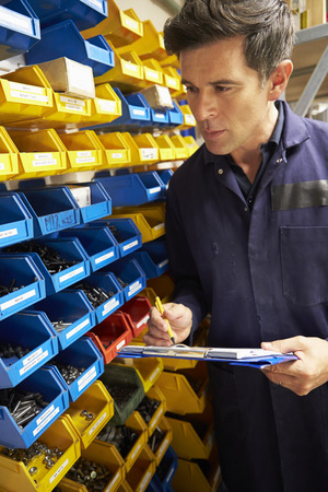 Worker Checking Stock Levels In Store Room