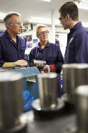 Engineer Working With Apprentices On Factory Floor photo