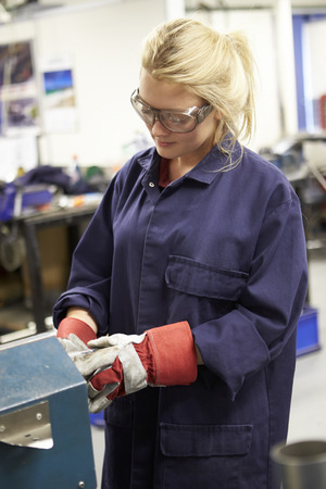 Apprentice Engineer Working On Factory Floor Фото со стока