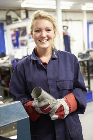 female engineer: Apprentice Engineer Working On Factory Floor Stock Photo