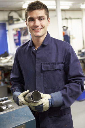 Apprentice Engineer Working On Factory Floor Archivio Fotografico