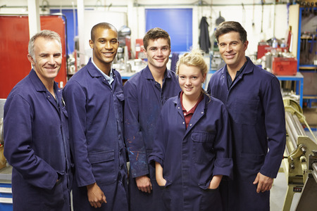 female engineer: Portrait Of Staff Standing In Engineering Factory