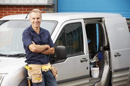 alba�il: Fontanero o un electricista de pie junto a Van Foto de archivo