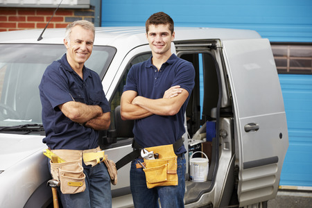 plumbing: Workers In Family Business Standing Next To Van