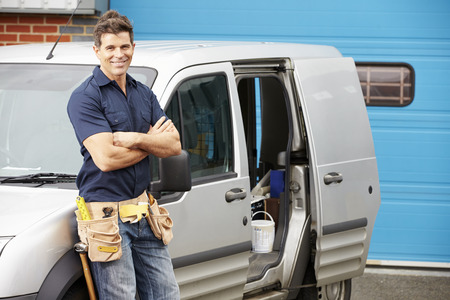 builder: Plumber Or Electrician Standing Next To Van Stock Photo