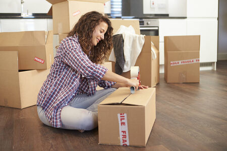 Woman Moving Into New Home And Unpacking Boxes photo