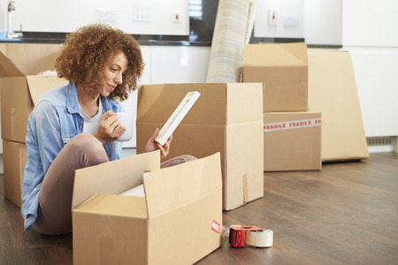 tea house: Woman Moving Into New Home And Unpacking Boxes