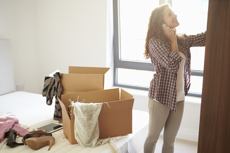 relocate: Woman Moving Into New Home Talking On Mobile Phone