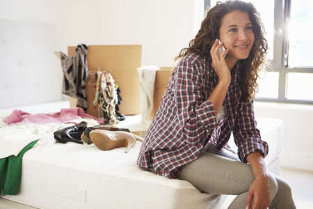 woman closet: Woman Moving Into New Home Talking On Mobile Phone