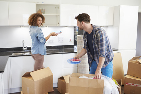 Couple Moving Into New Home And Unpacking Boxes photo