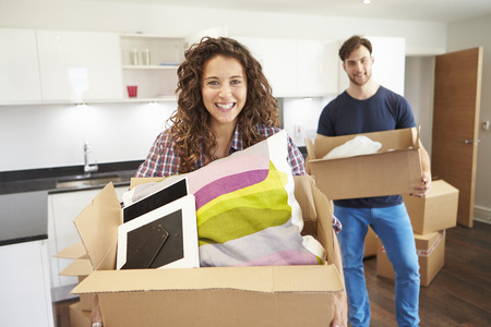 home interior: Couple Moving Into New Home And Unpacking Boxes