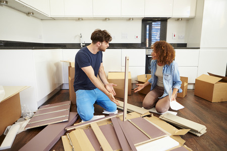 Couple Putting Together Self Assembly Furniture In New Home photo