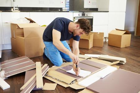 男の新しい家で自己アセンブリ家具を置くこと