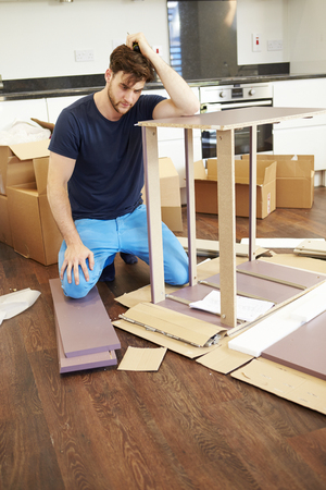 self assembly: Frustrated Man Putting Together Self Assembly Furniture