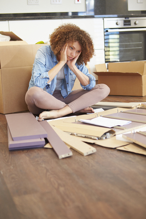 self assembly: Frustrated Woman Putting Together Self Assembly Furniture Stock Photo